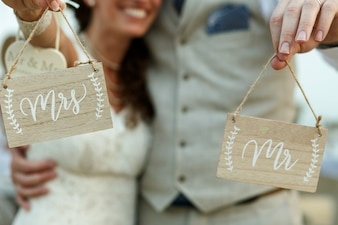 Happy newlyweds hold wooden boards with letterings 'Mrs' and 'Mr'