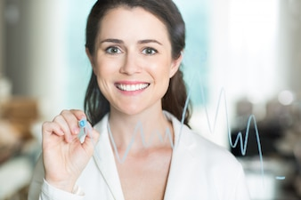 Happy Pretty Businesswoman Drawing Graph on Glass