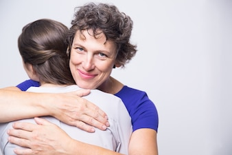 Happy senior woman embracing young adult daughter