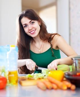 幸せな女性の野菜を切る