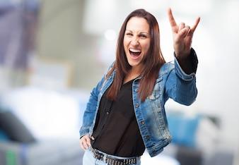 Happy woman doing rock gesture
