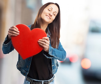 Happy woman in denim jacket with a giant heart