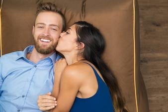 Happy woman kissing her husband lying on coach