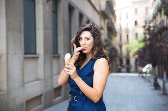 Счастливый женщина лизать пальцем во время еды мороженого