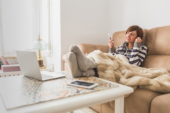 Happy woman listening to music on the sofa