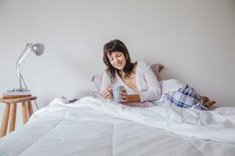 Happy woman lying on bed with coffee