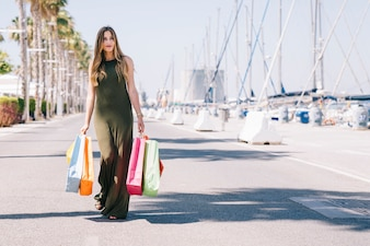 Happy woman posing with shopping bags on a sunny day
