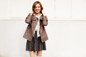 Happy woman posing with skirt and coat