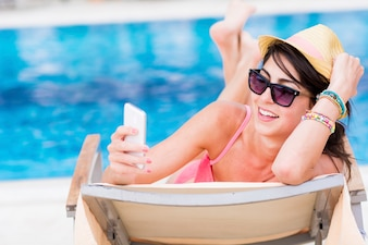 Happy woman using her mobile on the deck chair