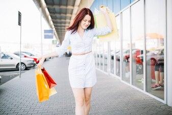Happy woman walking near shop-window