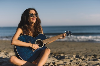 Happy woman with guitar at the beach