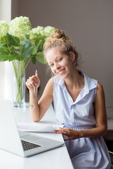Счастливая женщина, работающая с документами на подоконнике