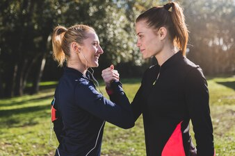 Happy women giving each other good luck before running