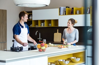 Happy young couple cooking together in the kitchen at home.