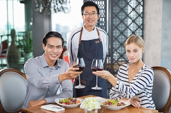 Happy Young Couple Drinking Red Wine in Restaurant