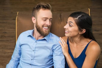 Happy young couple looking at each other on couch