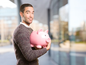 Happy young man holding a piggy bank