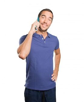 白い背景に携帯電話を使用している幸せな若い男