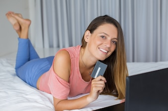 Happy young woman enjoying online shopping