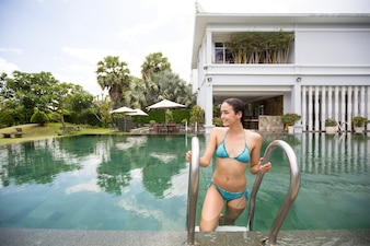 Happy young woman entering hotel outdoor pool