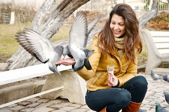 Happy young woman feeding pigeons