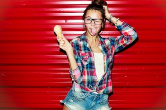 Happy young woman having fun and showing her tongue on red background