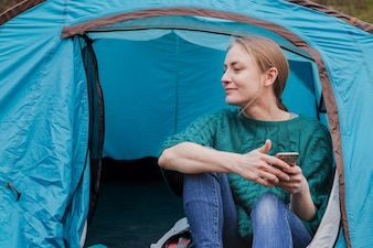 Happy young woman sitting in a tent