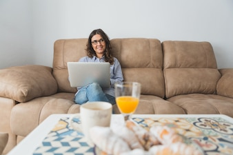 Happy young woman with laptop sitting on sofa