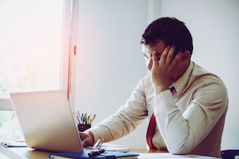 仕事の分析を考えるのは難しいです。若いアジア人のビジネスマンが明るいオフィスでプレッシャーに取り組んでいます。