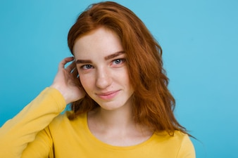 Headshot Portrait of happy ginger red hair girl with freckles smiling looking at camera. Pastel blue background. Copy Space.