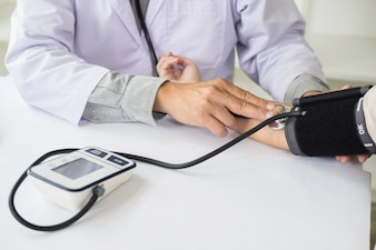 Healthcare, hospital and medicine concept - doctor and patient measuring blood pressure
