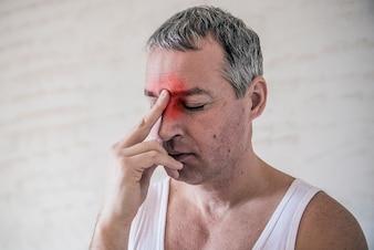 ヘルスケア、痛み、ストレス、年齢および人々のコンセプト - 家庭の頭痛に苦しむ成人。額に触れる男。否定的な人間の感情表情