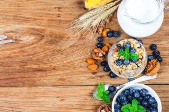 Healthy breakfast: oat granola with yogurt and fresh blueberries on wooden background