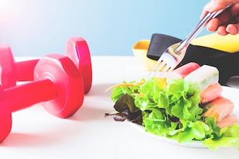 健康的な食事、ダイエット、菜食主義のキッチンと健康的な概念 - 家庭で野菜サラダロールとフォークのクローズアップ