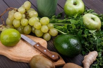 健康な緑色の野菜とスムージーのための果物は、テーブルの上に横たわる