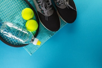 Healthy Life Sport Concept. Sneakers with Tennis Balls, Towel and Bottle of Water on Bright Blue Background. Copy Space.