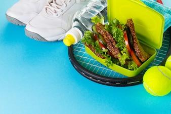 健康的なスポーツスポーツの概念。テニスボール、タオル、リンゴ、健康サンドウィッチ、明るい背景に水のボトルを持つスニーカー。スペースをコピーします。