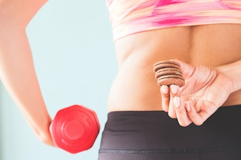 Healthy lifestyle concept, Diet and fitness, Fitness female holding snack and dumbbell in other hand