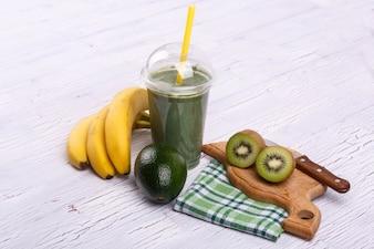 バナナ、ライム、ジンジャーがテーブルに横たわっている健康的なスムージー