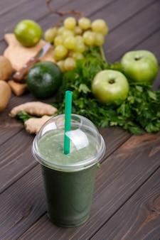 緑の野菜と果物を使った健康なスムージー、テーブルに横たわる