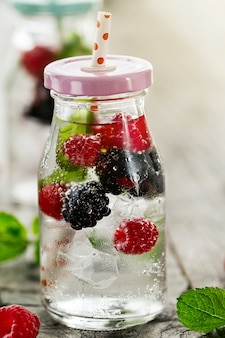 Healthy tasty fresh refreshing detox water in bottles or jars with raspberry, blackberry, mint and ice on wooden background. Closeup. Healthy Life Concept.
