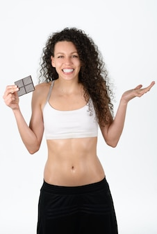 Healthy woman holding a piece of chocolate