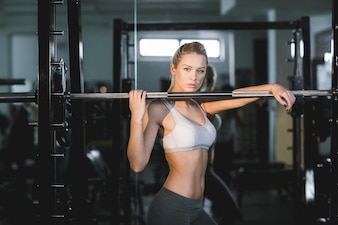 Healthy woman posing with a machine at the gym