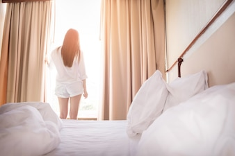 Healthy Woman stretching in bed room and open the curtains after wake up, back view, lifestyle people in cozy indoor comfortable relaxing space