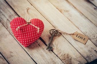 Сердце ткани и старинные ключ с ярлыком ярлык ЛЮБОВЬ на фоне деревянного стола.