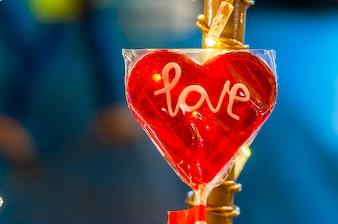 心臓赤い形のロリポップ、バレンタインハート、バレンタインデー。クリスマスの装飾 - ハート型のロリポップ、鮮やかなぼんやりした金色のボケの背景。