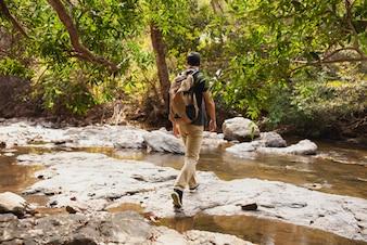 Hiker crossing river in nature
