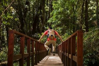 Hiker jumping on bridge