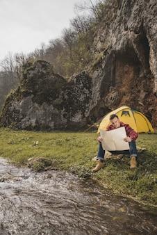 川の隣に座っている地図付きの登山人