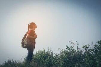 山、背景の青空、タイ、選択し、ソフトフォーカスの登山人の女性の双眼鏡を見て